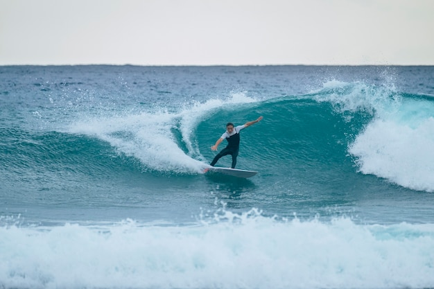 Um homem treinando e surfando nas férias de verão ou inverno usando roupa de neoprene - uma onda bonita e grande nas ilhas canárias