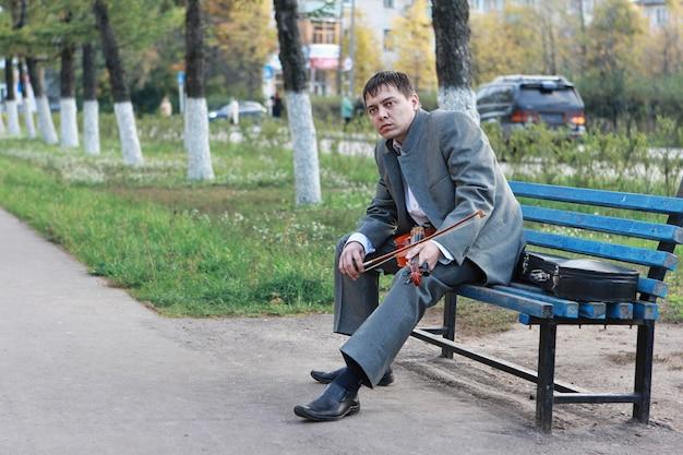 Um homem triste com um violino nas mãos está sentado em um banco