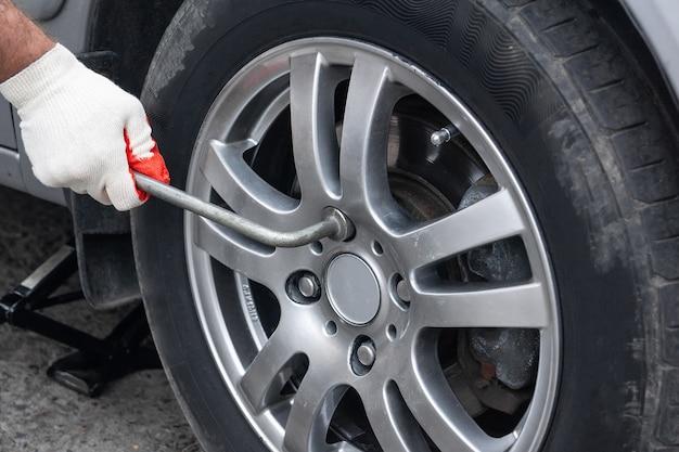 Um homem troca os pneus de verão do carro para o inverno