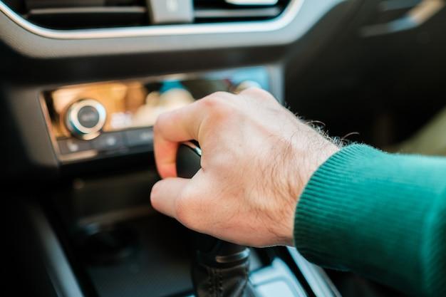 Um homem trocando a caixa de marchas no automóvel moderno, um homem trocando uma alavanca manual ou automática
