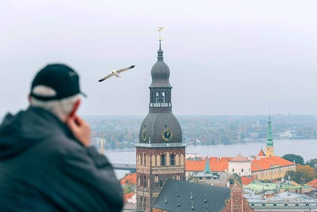 Um homem, turista no ponto de vista, panorama de riga e da catedral de riga na praça dome, letônia