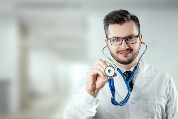 Um homem, um médico em um jaleco branco com um estetoscópio