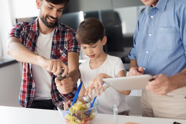 Um homem, um menino e um velho preparam uma salada.