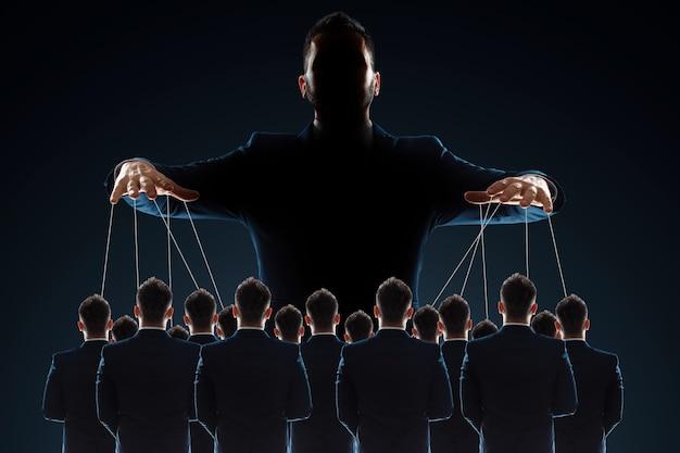 Um homem, um titereiro, controla a multidão com fios.