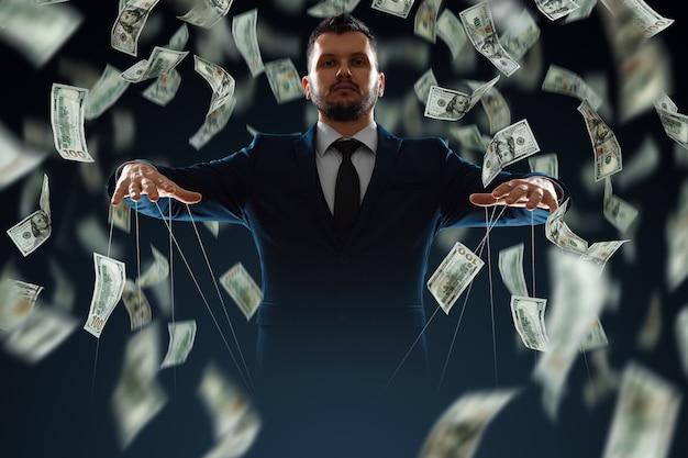 Um homem, um titereiro, ganha dinheiro por meio de manipulações.