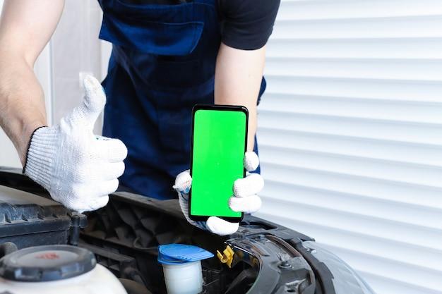 Um homem uniformizado conserta um carro e segura um smartphone com uma tela verde e mostra como