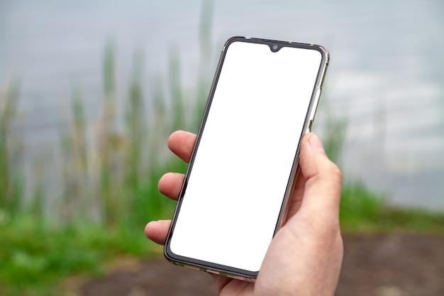 Um homem usa seu smartphone na margem de um lago
