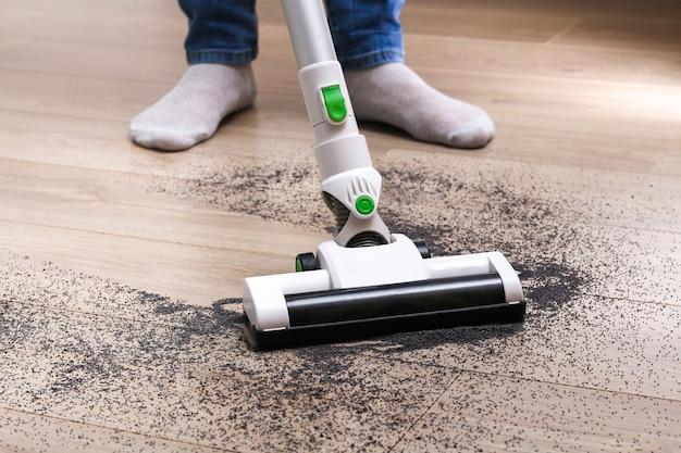 Um homem usa um aspirador de pó sem fio vertical sem saco para limpar o chão.