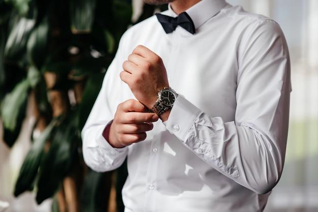 Um homem usa um relógio na mão