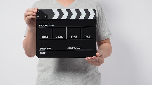 Um homem usa uma camiseta cinza e a mão está segurando uma claquete preta ou uma tela de cinema. é usado na produção de vídeo ou na indústria do cinema. é o fundo branco.