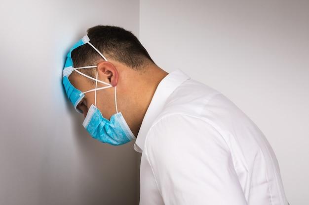 Um homem usando máscaras médicas descartáveis inclinou a cabeça contra o conceito de parede em depressão devido à quarentena