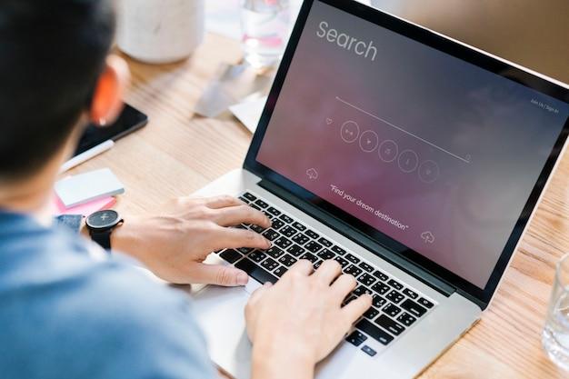 Um homem usando um laptop para pesquisar informações