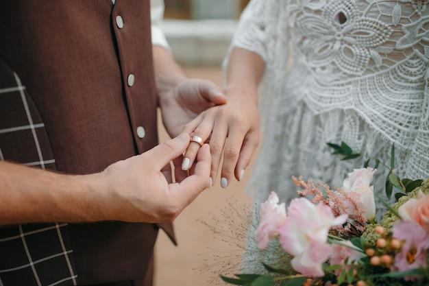 Um homem usando uma aliança no dedo de sua esposa