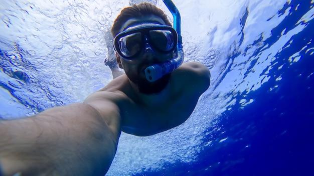 Um homem usando uma máscara e um tubo de respiração mergulhou nas profundezas do mar vermelho e está tentando nadar