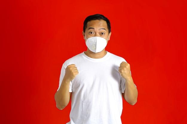 Um homem usando uma máscara médica cerrou as mãos enquanto olhava para a frente com uma expressão de sucesso