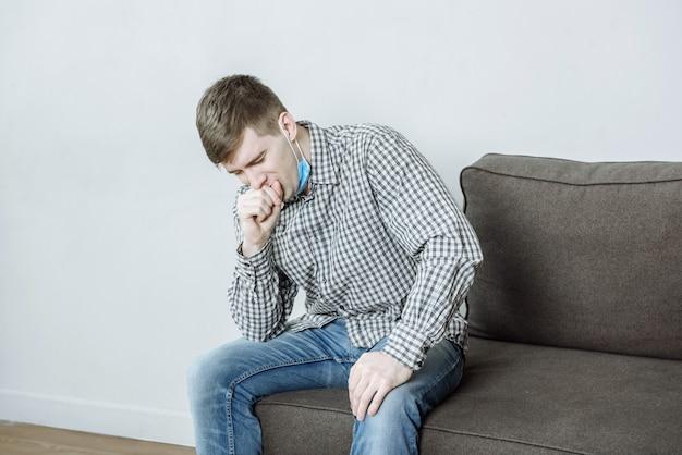 Um homem usando uma máscara protetora tosse com sintomas do coronavírus covid-19