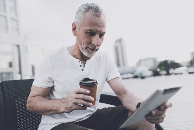 Um homem velho com uma barba senta-se em um sofá na rua