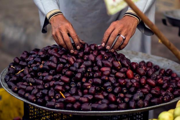 Um homem vendedor toca datas frescas no prato no mercado de frutas