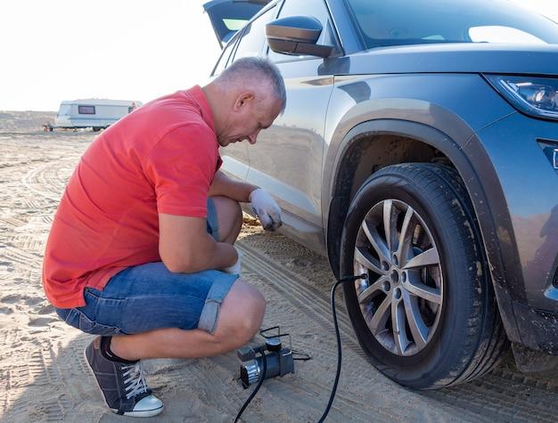 Um homem verifica a pressão dos pneus. viaje para o mar de carro.
