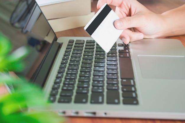 Um homem veste as camisas de manta azul que compram em computadores e pagam pelo cartão de crédito.
