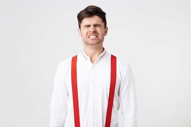 Um homem vestido com uma camisa branca e suspensórios vermelhos, franze os olhos, mostrando, apertando os dentes brancos