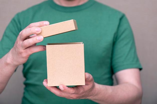 Um homem vestido com uma camiseta verde segurando uma pequena caixa de papelão aberta