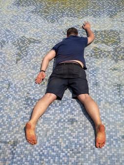 Um homem vestido deita-se em uma piscina vazia durante o dia e finge que está nadando. uma piada relaxa