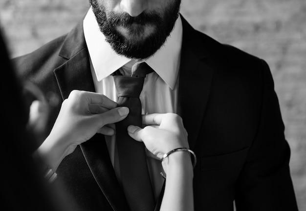Um homem vestindo-se com a ajuda de uma namorada