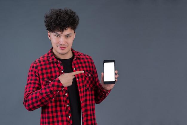Um homem vestindo uma camisa xadrez vermelha com um smartphone
