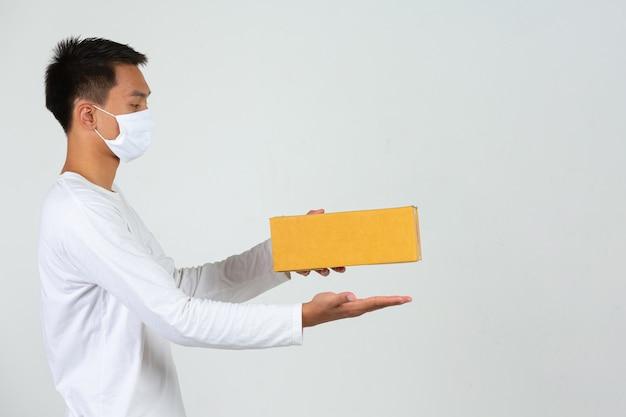 Um homem vestindo uma camiseta branca está segurando uma caixa de correio marrom para entregar coisas faça gestos e expressões faciais.