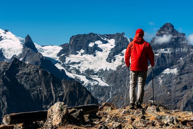 Um homem viajando no cáucaso. esportes de montanha. final feliz do atleta. turismo de montanha. passeio a pé. a jornada para as montanhas. caminhada nórdica entre as montanhas. copie o espaço