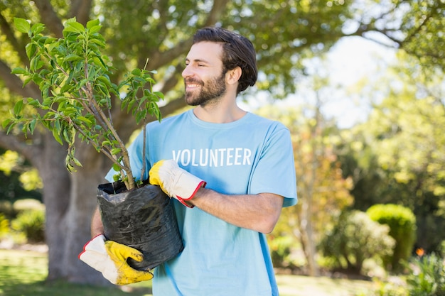 Um homem voluntário segurando a planta