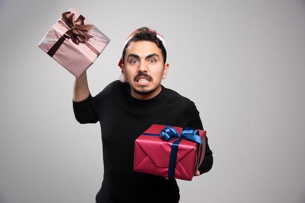 Um homem zangado com um chapéu de papai noel segurando um presente de ano novo.