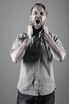Um homem zangado grita com um filme no pescoço
