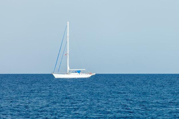 Um iate branco solitário com velas rebaixadas fica nas águas do mar mediterrâneo