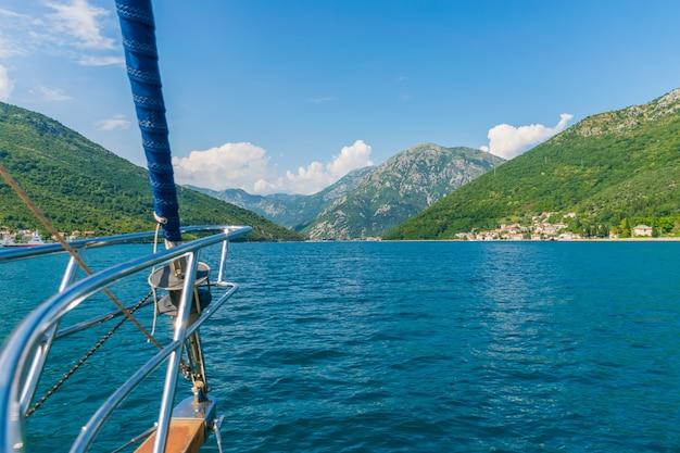 Um iate de luxo navega ao longo da pitoresca baía de kotor, em montenegro.