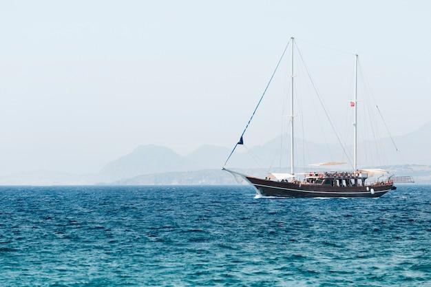 Um iate turístico com turistas no mar. bela viagem de verão no mar ao sol da manhã.
