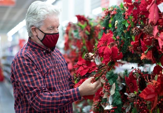 Um idoso de cabelos brancos escolhendo uma guirlanda de natal em uma loja para as próximas férias, usando uma máscara vermelha devido à infecção por coronavírus