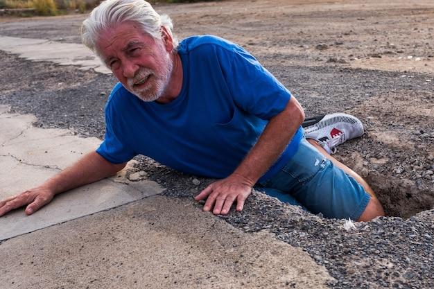 Um idoso ou aposentado caiu no chão porque enfiou o pé num buraco na rua - homem maduro precisando de ajuda na estrada - problema para um aposentado