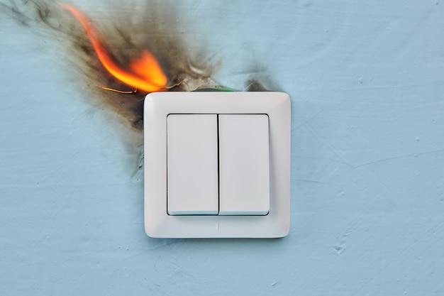 Um incêndio elétrico está começando em casa devido a uma tomada elétrica com defeito.