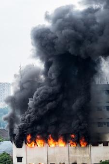 Um incêndio irrompeu no armazém e a brigada de incêndio apagava o fogo.