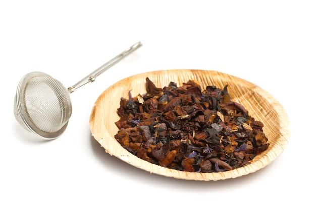 Um infusor de chá e um prato com chá seco em um fundo branco
