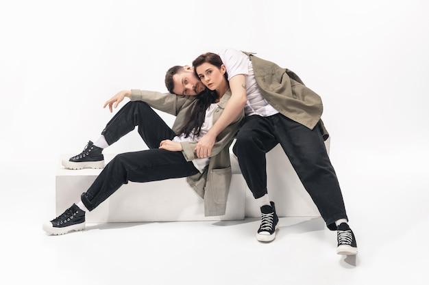 Um inteiro. casal na moda moderno isolado no fundo branco do estúdio. mulher caucasiana e homem posando com roupas elegantes mínimas básicas. conceito de relações, moda, beleza, amor. copyspace.