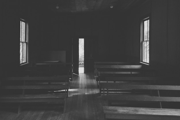 Um interior de uma pequena igreja na zona rural com bancos de madeira e uma porta aberta