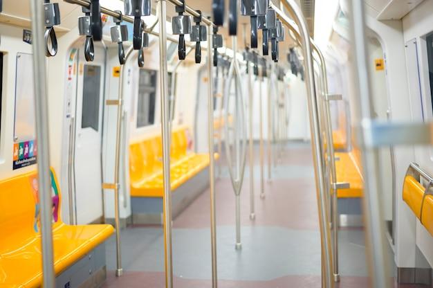 Um interior vazio de assentos de passageiros no trem do metrô.
