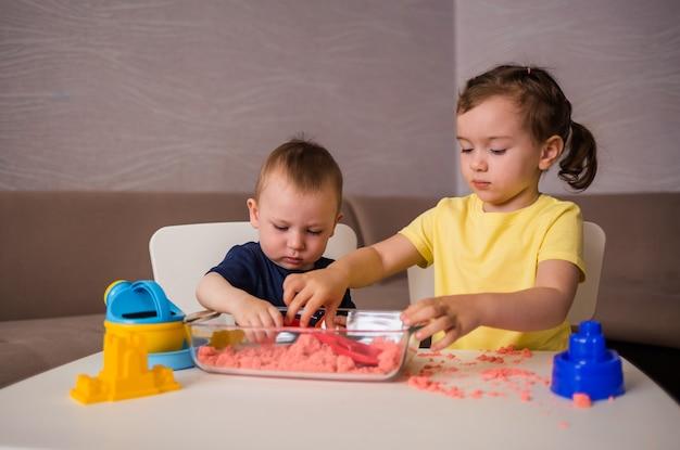 Um irmão e uma irmã brincam em uma mesa com areia cinética. toque em jogos em casa.