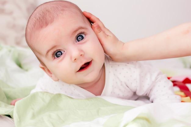 Um irmão gentil toque na bochecha do bebê. pele saudável
