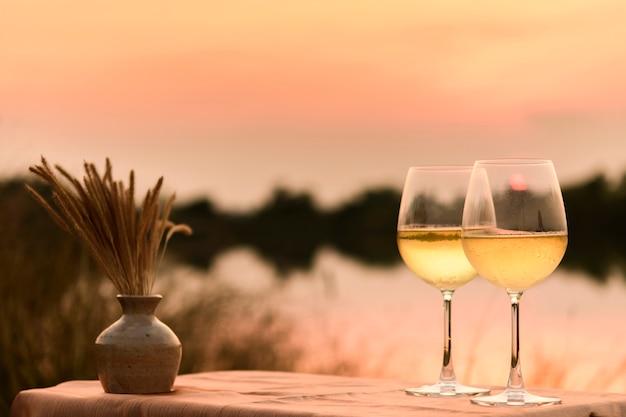 Um jantar romântico no verão em uma praia ao pôr do sol com dois copos de vinho branco
