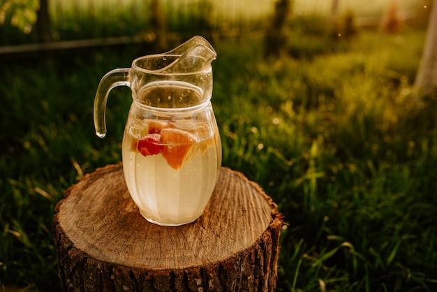 Um jarro de vidro com limonada e frutas dentro está de pé sobre um toco de madeira. ao pôr do sol em um fundo de grama verde. morangos, laranja, limão e tangerina.