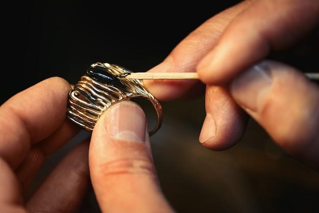 Um joalheiro está colando a gema preciosa no anel de ouro.